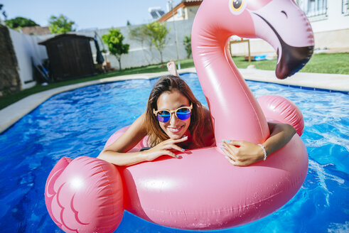 Portrait of happy young woman with pink flamingo float in swimming pool - KIJF01530