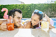 Happy couple in swimming pool with drinks at the poolside - KIJF01533