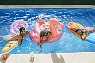 Happy friends on floats in swimming pool - KIJF01536