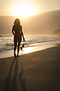 Mexico, Riviera Nayarit, silhouette of woman walking into the sunset at a beach while holding her bikini top - ABAF02164