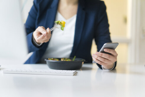 Businesswoman eating lunch in office - JOSF01130