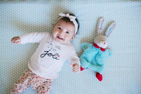 Happy baby girl lying on bed beside toy bunny - GEMF01668