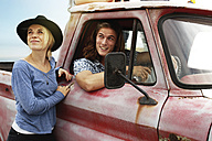 Smiling young couple with an old pick up - ZEF13882