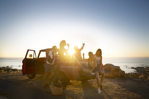 Happy young people outside pick up truck at the coast at sunset - ZEF13915