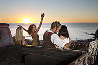 Young people outside pick up truck at the coast enjoying the sunset - ZEF13921