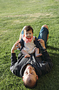 Cute baby girl sitting on her father's belly in a meadow - GEMF01673