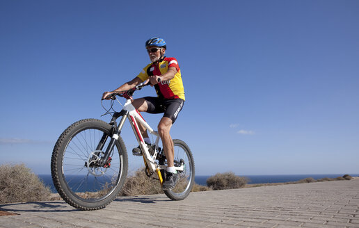 Spain, Canary Islands, Fuerteventura, senior man on mountainbike - MFRF00842