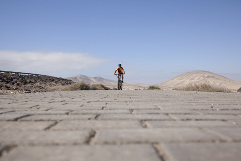 Spain, Canary Islands, Fuerteventura, senior man on mountainbike - MFRF00845