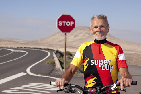 Spain, Canary Islands, Fuerteventura, portrait of confident senior man with mountainbike - MFRF00848