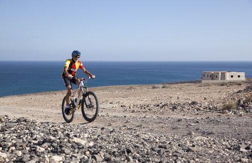 Spain, Canary Islands, Fuerteventura, senior man on mountainbike - MFRF00851