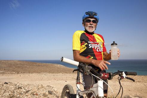 Spain, Canary Islands, Fuerteventura, senior man with mountainbike having a rest - MFRF00854
