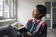 Smiling woman sitting at the window with notebook - KNSF01520