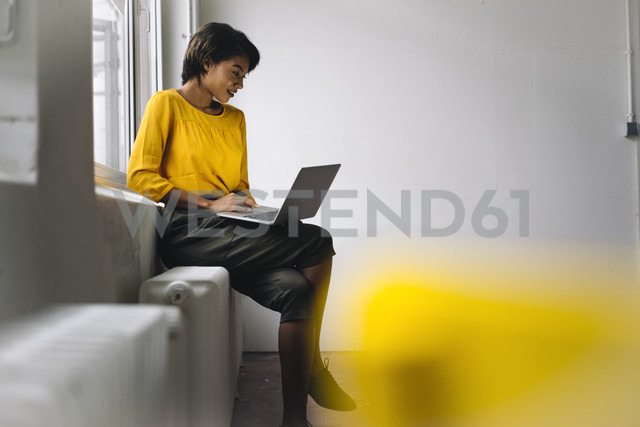 Woman sitting at the window using laptop - KNSF01538 - Kniel Synnatzschke/Westend61