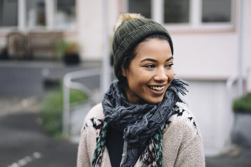 Smiling young woman wearing wooly hat outdoors - KNSF01541