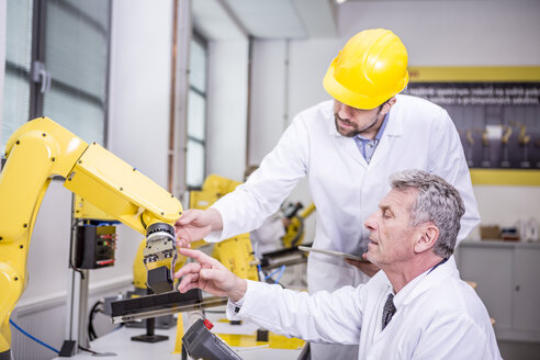 Two engineers examining industrial robot - WESTF23397