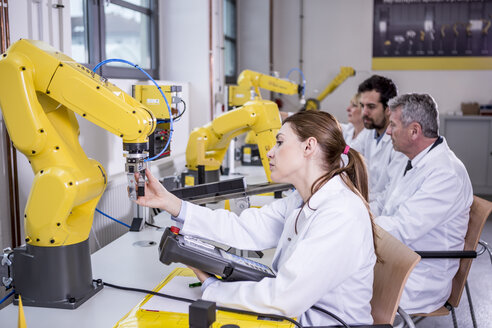 Engineers examining industrial robots - WESTF23406