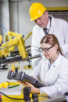 Two engineers in factory looking at device - WESTF23409