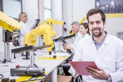 Portrait of smiling engineer in factory with clipboard - WESTF23415