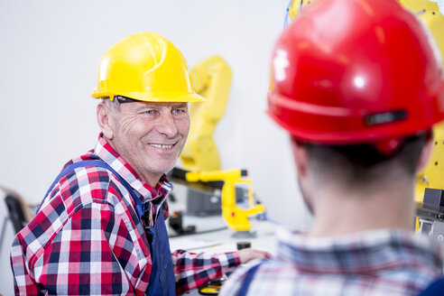 Man in factory wearing hard hat smiling at colleague - WESTF23424