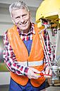 Portrait of smiling technician adjusting industrial robot - WESTF23436