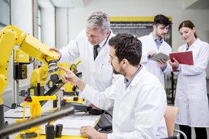 Engineers examining industrial robot - WESTF23439