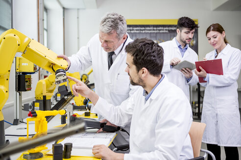Engineers examining industrial robot - WESTF23439