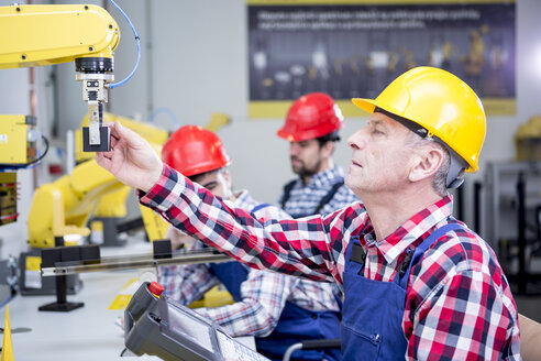 Man wearing hard hat adjusting industrial robot - WESTF23448