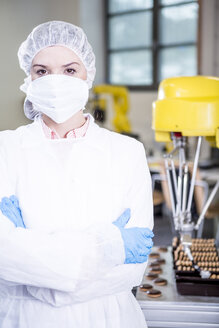Portrait of woman in protective workwear with robot handling cookies in background - WESTF23454