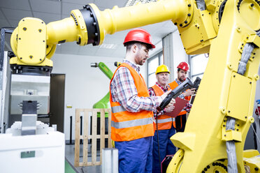 Three men in factory with industrial robot - WESTF23457