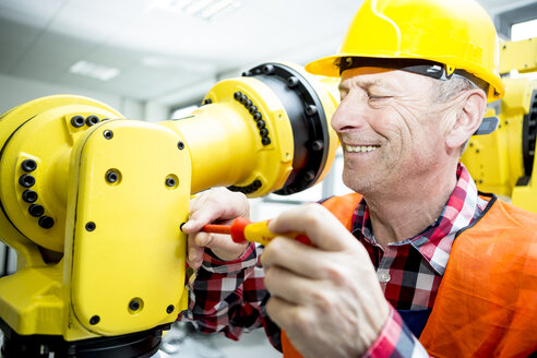 Smiling technician working on industrial robot - WESTF23463