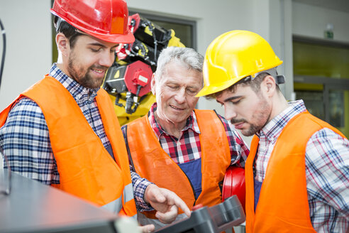 Three men in factory talking with industrial robot in background - WESTF23466