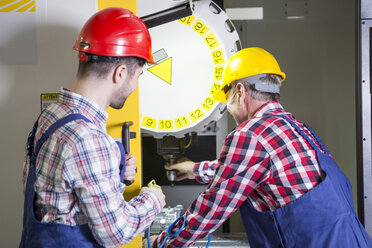 Two men in factory working at CNC machine - WESTF23472
