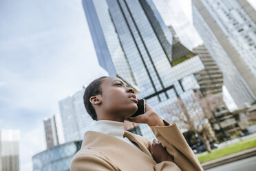 France, Paris,  Young businesswoman talking on the phone - KIJF01546