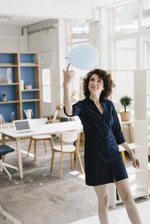 Businesswoman in office balancing balloon on finger - KNSF01545