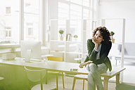 Businesswoman in office sitting on desk, looking worried - KNSF01554