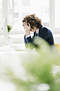 Businesswoman in office burying head in hands - KNSF01557