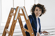 Businesswoman standing by ladder in office, holding smartphone - KNSF01560