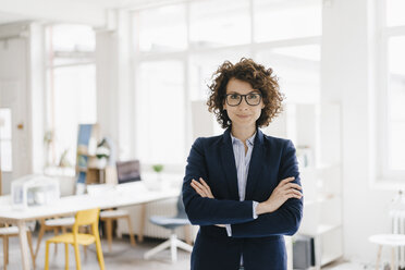 Businesswoman standing in her office with arms crossed - KNSF01566