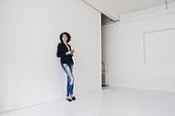 Businesswoman standing in loft , leaning against wall - KNSF01569