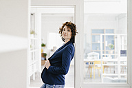 Businesswoman standing in her office, leaning in door frame - KNSF01575