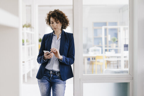 Businesswoman standing in office door, using smartphone - KNSF01578