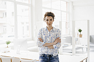 Businesswoman in office sitting on desk, looking confident - KNSF01590