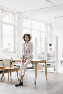 Businesswoman in office sitting on desk, looking confident - KNSF01599