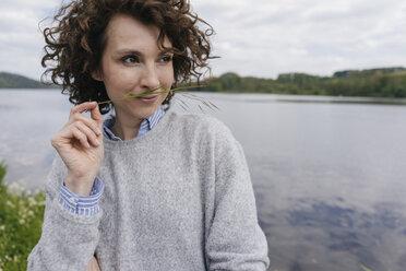 Woman at lakeshore, smelling grass blade - KNSF01620