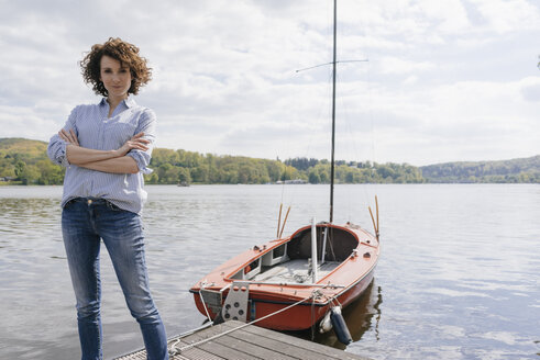 Woman standing on jetty with moored sailing boat - KNSF01626