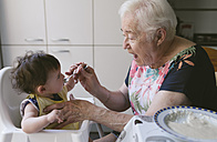 Grandmother feeding baby girl in the kitchen - GEMF01679