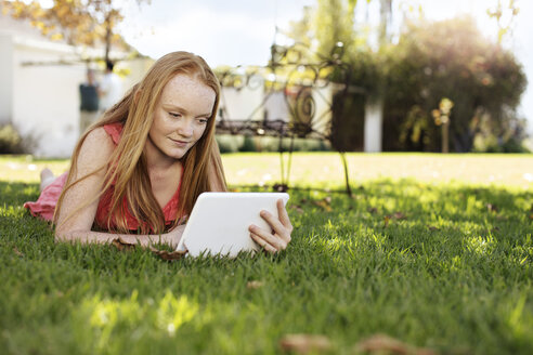 Grl with long red hair lying in grass with tablet - ZEF13929