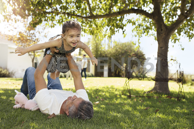 Father playing with daughter in garden - ZEF13932