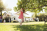 Girl wearing a red dress spinning around outside on the lawn - ZEF13935