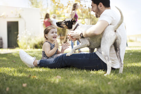 Happy father, daughter and dog in garden - ZEF13938